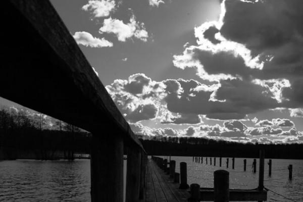 Sort hvid bådbro med skyer af Niels Foltved